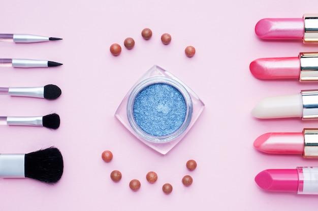 プロの化粧道具。コピースペースとピンクのパステル調の背景に口紅赤面アイシャドウをブラシします。フラットレイ