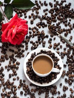 咲く赤いバラのコーヒーカップ、コンクリートの下の背景にコーヒー豆。