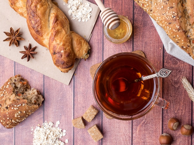 Зерновой хлеб с медом и орехами, кружка чая коричневого сахара на фоне темных деревянных.