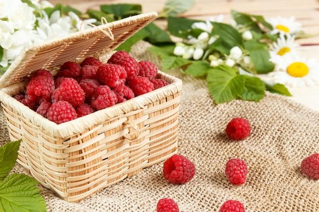 枝編み細工品箱の中の新鮮なラズベリーと蜂蜜、緑の葉。