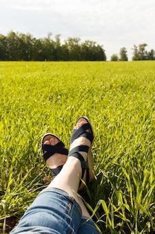 緑の芝生の上の金のサンダルと足。リラックス。