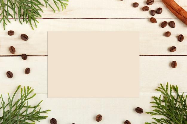 コーヒーカップ、コーヒー豆、木製の背景に小ぎれいなな枝。