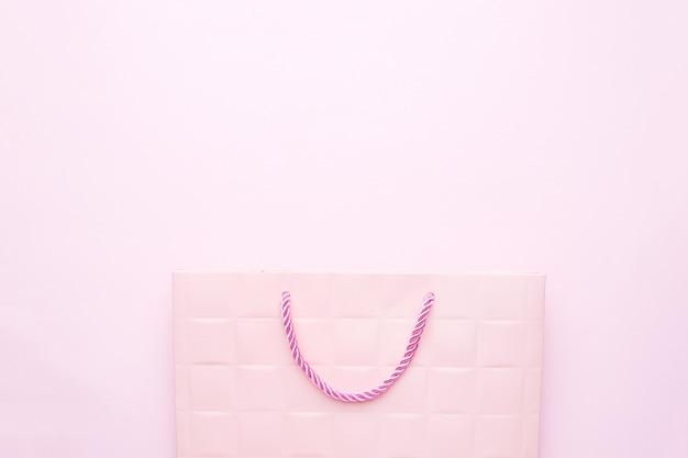 コピースペースとピンクの背景にピンクの紙のギフトバッグ。