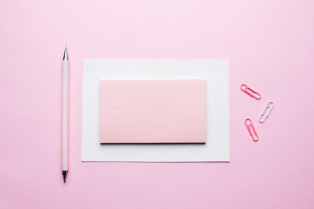 ピンクのパステル調の背景上のテキストにピンクのメモ帳。