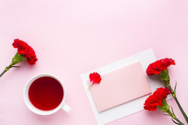 赤ピンクのオブジェクト。一杯の紅茶、カーネーションの花パステルピンクの背景上のテキストのメモ帳。