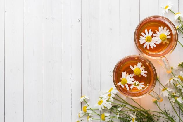 木製の背景にお茶とカモミールの花のカップ