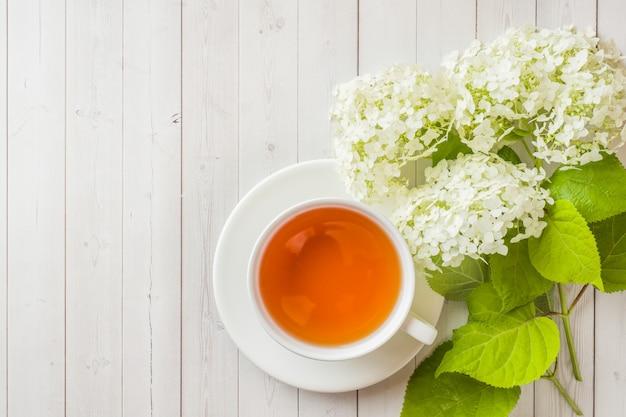 花とテーブルの上の紅茶のカップ。朝居心地の良い朝食。コピースペース