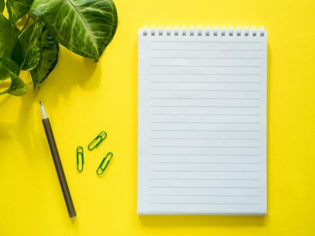 メモ帳、黄色のデスクトップ上の緑の植物の葉、フラットレイアウト、コピースペース用のメモ帳。