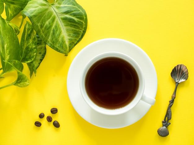 緑の葉は黄色のデスクトップ、フラットレイアウト、コピースペースにコーヒーカップを植える。