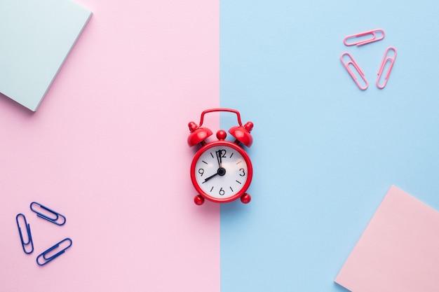 フラットメモ帳のペーパークリップの赤い目覚まし時計でパステルピンクとブルーの背景に横たわっていた