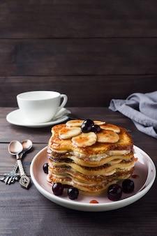 バナナとベリーのシロップ、セレクティブフォーカス、暗い背景とケーキをパンケーキします。