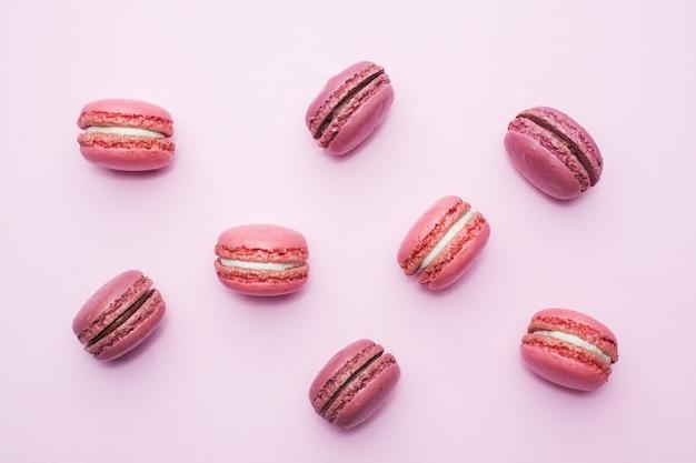 ピンクのデザートマカロンまたはマカロンの平らな平面図とピンクの背景平面図