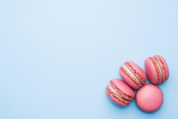 ピンクのデザートマカロンまたはマカロンの青い背景上の平面図