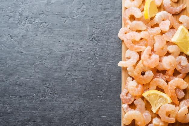 Креветка со специями и лимоном на деревянной доске. темный фон с копией пространства
