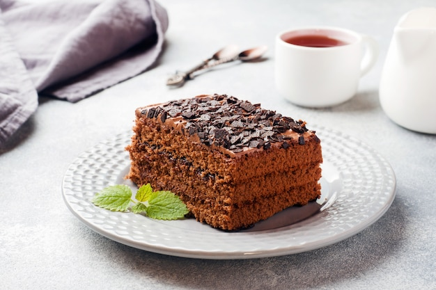 Кусок трюфельный торт с шоколадом на сером фоне бетона.