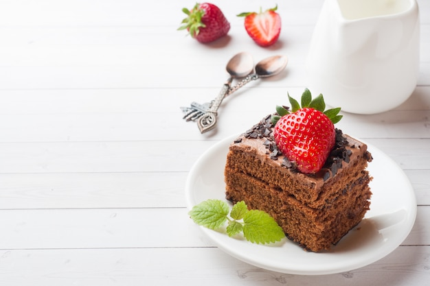 Трюфельный торт с шоколадом и клубникой и мятой на белом деревянном столе.