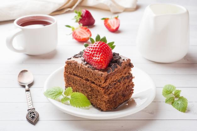 Трюфельный торт с шоколадом и клубникой и мятой на белом деревянном столе. выборочный фокус.