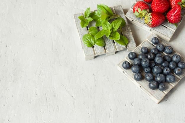 Свежие ягоды клубники черники мяты на деревянной подставке, серый фон