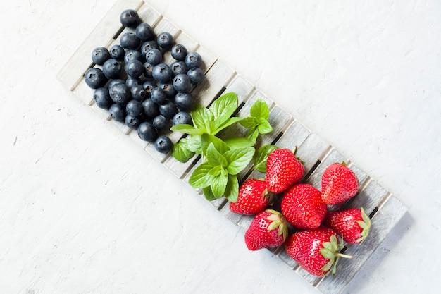 Свежие ягоды клубники черники мяты на деревянной подставке