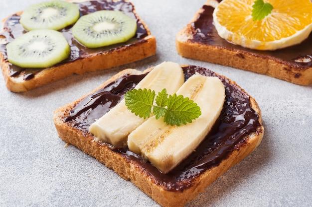 チョコレートペーストとグレーのテーブルの上の様々な果物のサンドイッチ。