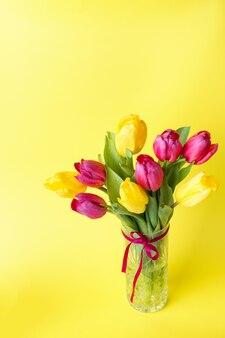 黄色の背景に黄色とピンクのチューリップの花束。コピースペース
