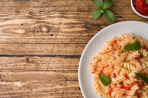 Спиральная паста с помидорами черри и томатным соусом на тарелке.