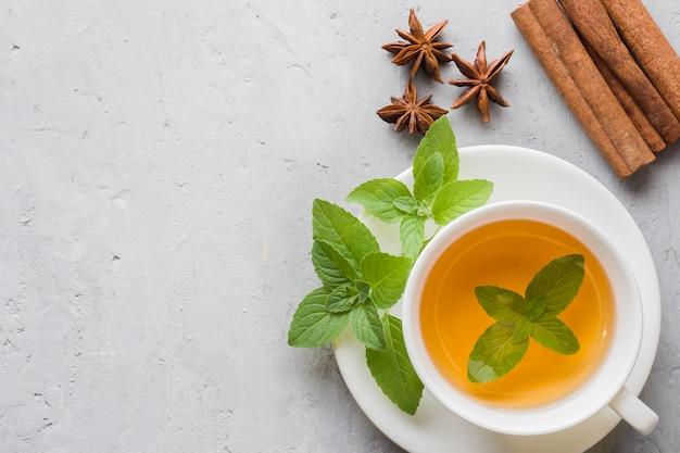 Чашка чая со свежими листьями мяты и корицей на сером бетоне