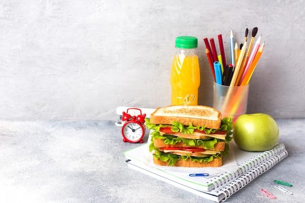 Здоровый обед для школы с бутербродом, свежим яблоком и апельсиновым соком.