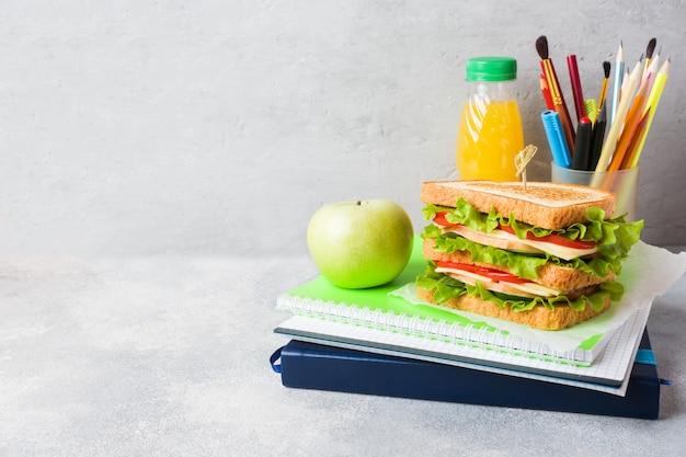 サンドイッチ、新鮮なリンゴ、オレンジジュースを使ったヘルシーなランチ。