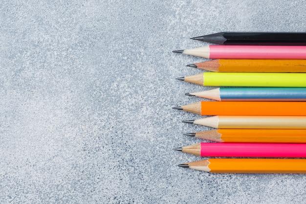 グレーのテーブルの上の明るい色鉛筆。コンセプトスクール。コピースペース