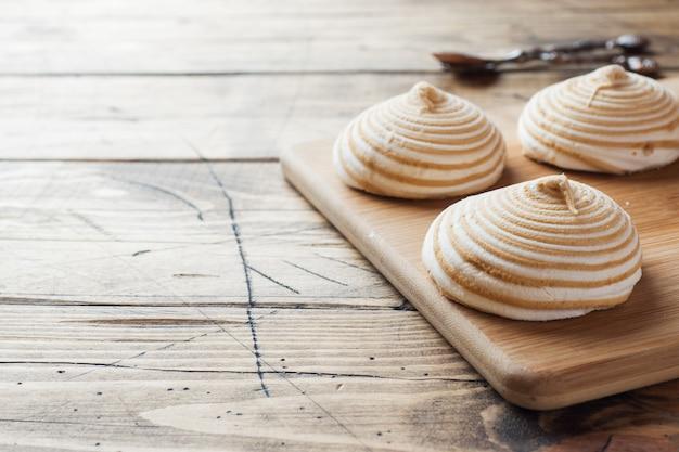 Зефир ванильный зефир с карамелью на деревянном столе.