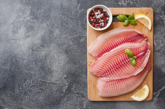 レモンとスパイスをまな板の上のティラピアの生の魚の切り身。コピースペースを持つ暗いテーブル。