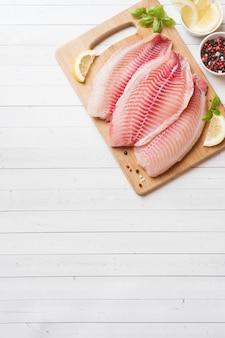 レモンとスパイスをまな板の上のティラピアの生の魚の切り身