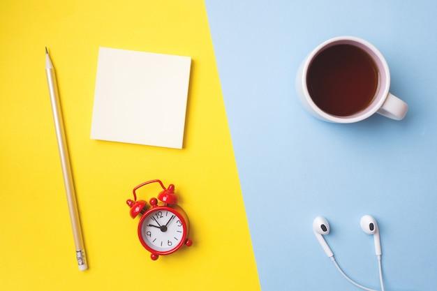 ステッカー文房具、一杯のコーヒー、黄色い青いテーブルの上の時計
