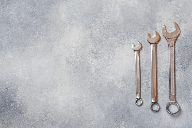 Гаечные ключи, инструменты на сером фоне бетона с копией пространства.