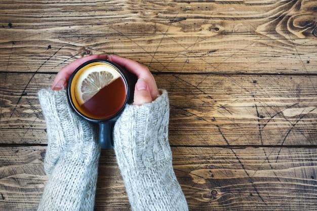 寒い日にレモンと紅茶のカップを持つ女性の手。木製のテーブル上面図。