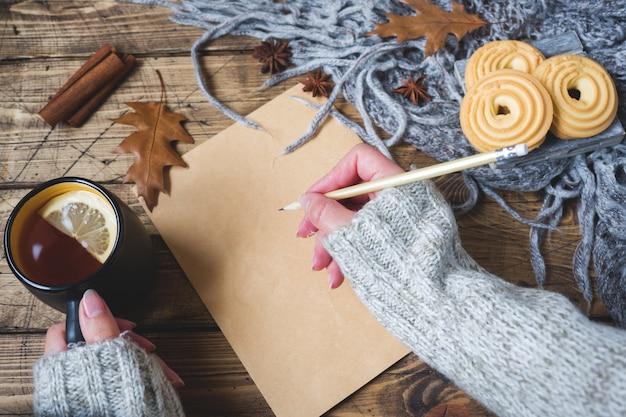 一杯の紅茶、クッキー、セーター、木の表面の葉の秋のある静物。居心地の良い秋の概念