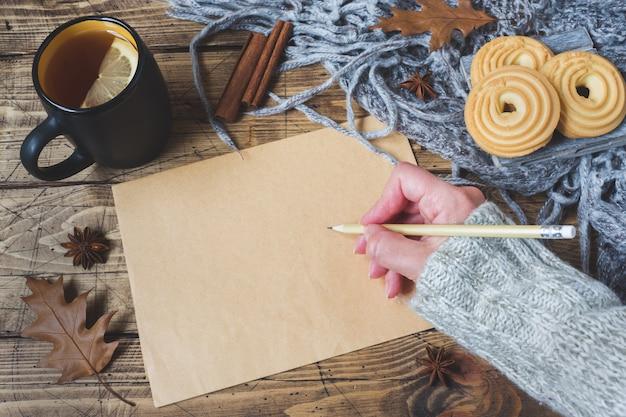 一杯の紅茶、クッキー、セーター、木の表面の葉の秋のある静物。居心地の良い秋、テキスト用のフォームの概念。ペンを持つ女性の手