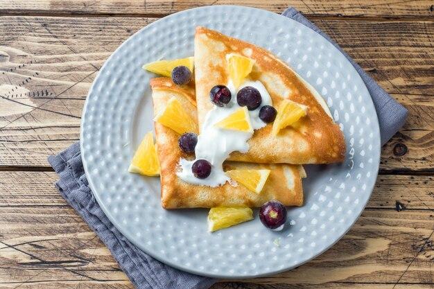 皿の上の果実とクリームとパンケーキの一部。