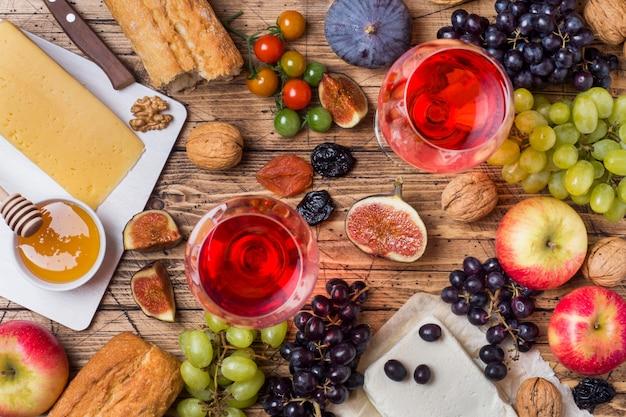 素朴な木製のテーブルの上にチーズ、ワイン、バゲットグレープが蜂蜜と軽食を添えています。