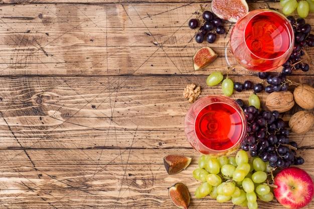 Сыр, вино, багет, виноград, инжир, мед и закуски на деревенском деревянном столе с копией пространства.
