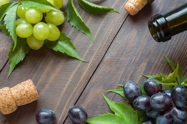 赤と白のブドウ、ワインとコルクの木製のテーブル背景に瓶の束