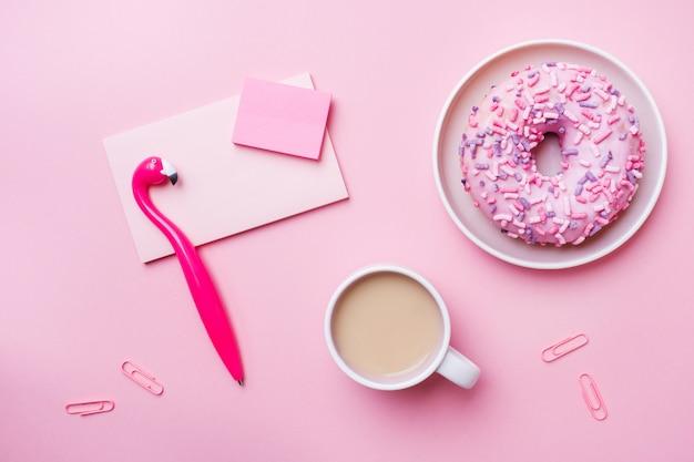 Чашка кофе, пончик перо фламинго блокнот на розовый. концепция офиса. квартира лежала.
