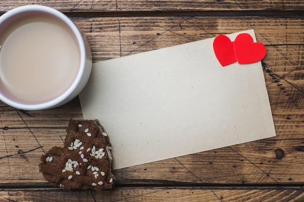 コンセプトバレンタインデー。一杯のコーヒーと木製のテーブルの上のクッキー。グリーティングカード。コピースペース