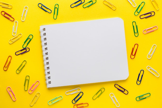 空白のノートブックと黄色の色のペーパークリップ