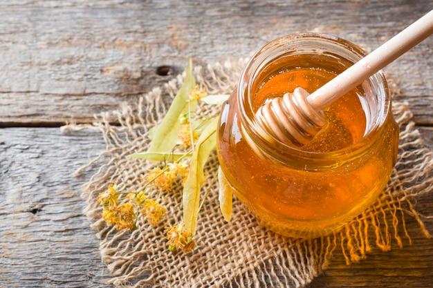 蜂蜜のガラス瓶、木の表面にリンデンの花