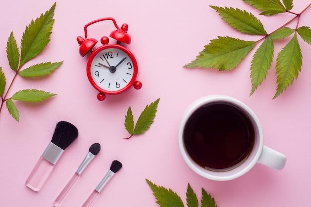 Кисти для макияжа, чашка кофе и часы. концепция красоты.