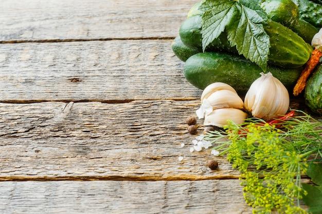 キュウリのピクルス、ニンニク、スパイス、木製のテーブルの上の瓶にピクルス。