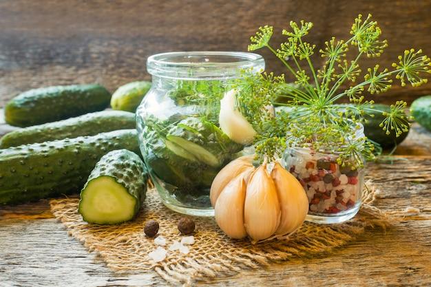 Маринованные огурцы, чеснок и специи для маринования в банке на деревянном столе.