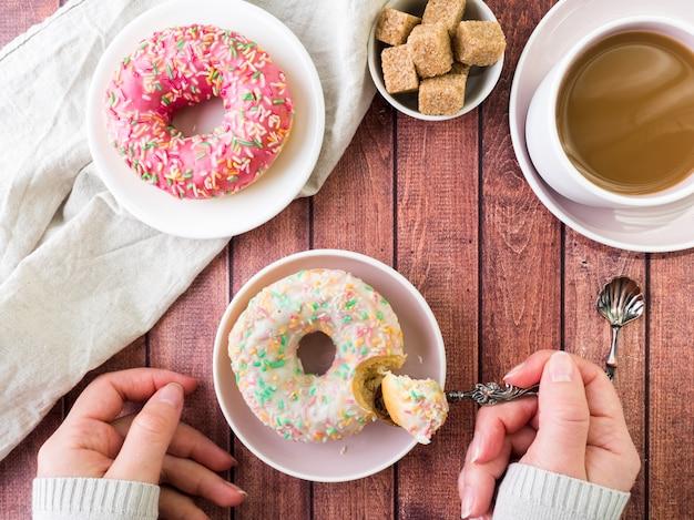 ドーナツと木製のテーブルの上のコーヒー。コピースペース平面図。